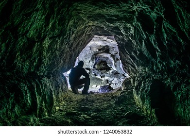 Silhouette of a man in an old phosphor mine tunnel