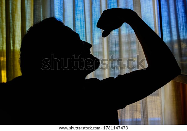Silhouette of a man on background of window.