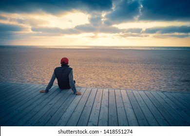 Silhouette of man on the beach looking at magical sunset. Man sitting on the wooden terrace