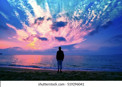 Silhouette of man on the beach looking at magical sunset.