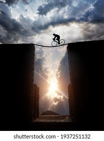 Silhouette of a man on bicycle Cycling over the abyss at sunset cloudy sky background