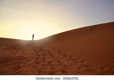 Silhouette of Man on Desert Sand during Sunrise. Loneliness and Success Symbolism.