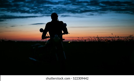 The silhouette of a man on a motorbike at sunset