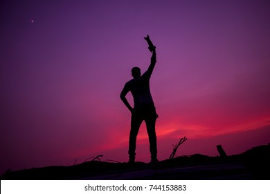 Silhouette of a man on the rock at sunset on Jeddah Saudi Arabia