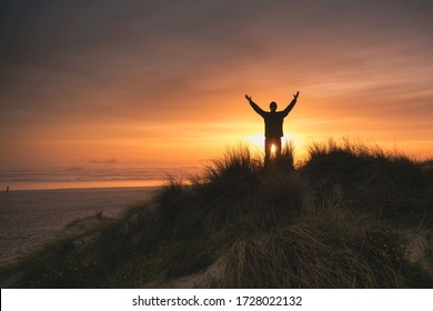 Silhouette man on the sand dunes at sunset