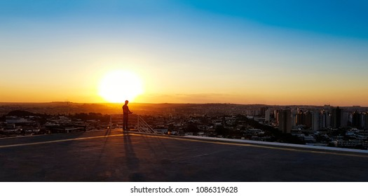Silhouette of a man on top of a building. Sunset on the city in the background.