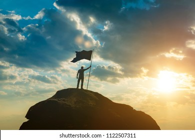 Silhouette of a man on top of a mountain with the flag of victory. Against the background of the sky in the sunset. High achievements, success in business, leadership, businessman