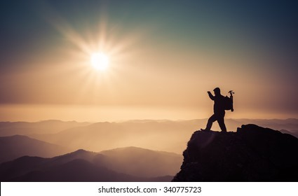 silhouette of a man on the top of the mountain with sun in the frame