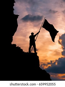 Silhouette of a man on top of a mountain with a national flag of victory! The idea: patriotism, sport victory, business success.