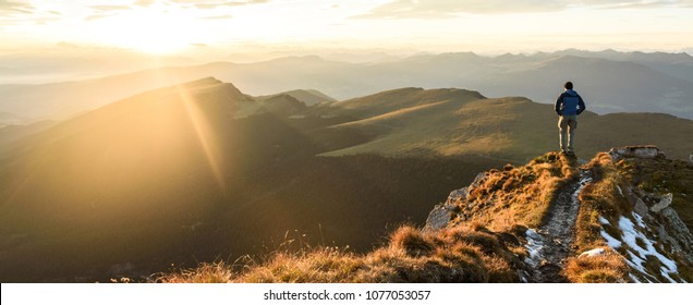 Silhouette of the man on top the peak of mountain on sunrise sky , Sport and active life conceptual design.