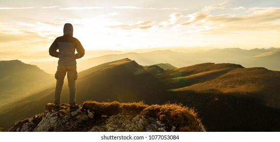 Silhouette of the man on top the peak of mountain on sunrise sky , Sport and active life onceptual design.
