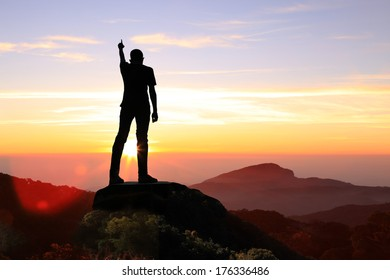 Silhouette of the Man on top the peak of mountain on sunrise sky , Sport and active life, Conceptual design.