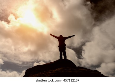 Silhouette of a man on the top of a rock meeting sun - success concept