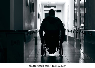 Silhouette of man on wheelchairs in corridor of hospital