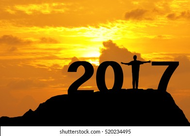 Silhouette of a man open hands on top of mountain during sunset to complete 2017 year.
