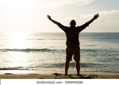 Silhouette of a man with outstretched arms and facing the sun and ocean
