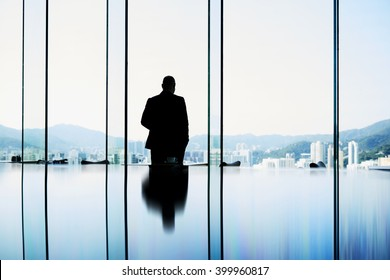Silhouette of a man owner of trading company in real estate is looking into window and thinking about future meeting with client. Intelligent male professional banker is standing in conference room