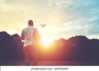 Silhouette of a man photographer is shooting video with multirotor RC quadcopter, while is standing against sunset and alp. Young male is taking photo on modern flying remote camera during summer trip
