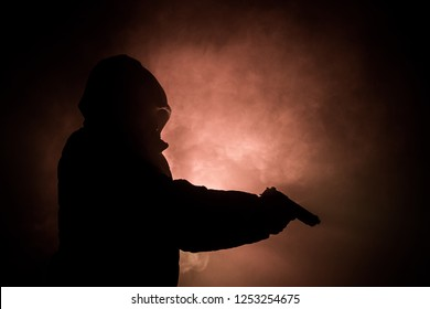 Silhouette of man with pistol ready to attack on dark toned foggy background or dangerous bandit holding gun in hand. Shooting terrorist with weapon theme decor