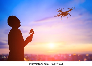 silhouette of man play drone in the sunset, asian