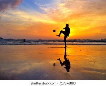 Silhouette of man playing football on the beach.