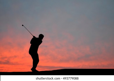 Silhouette of man playing golf, sun, beautiful colorful sky and clouds behind. Golfer hitting golf ball down the fairway  with club on course during sunset.