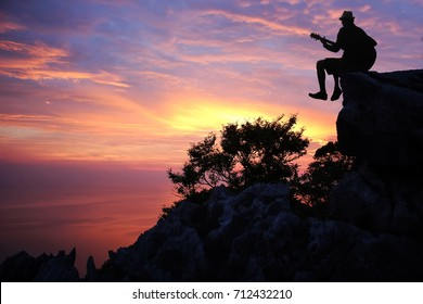Silhouette man playing a guitar on the mountain with sunset sky background.