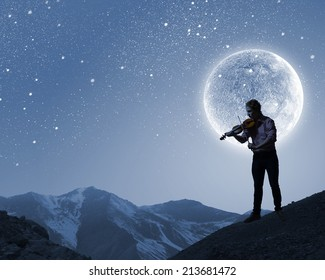 Silhouette of man playing violin at night