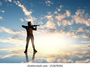 Silhouette of man playing violin at sunset