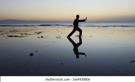 Silhouette of man practiceing qigong exercises at sunset by the sea