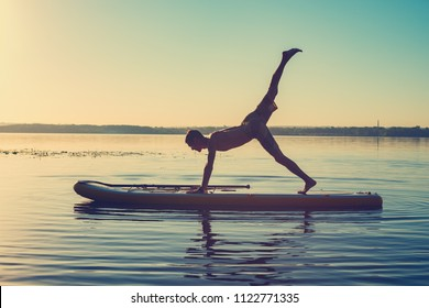 Silhouette of man practicing yoga on a SUP board during sunrise on a large river. Stand up paddle boarding - awesome active recreation in nature.