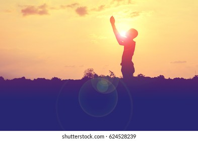 Silhouette of man pray with sunset background