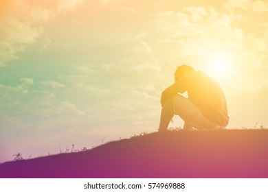 Silhouette of man praying over beautiful sky background