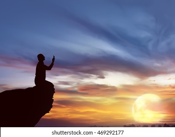 Silhouette of man praying at sunset. He pray to god.
