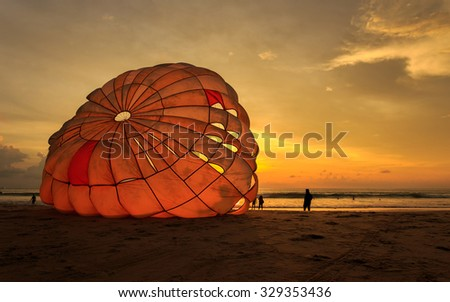 Silhouette of man is preparing para sailing at the sunset beach in Thailand