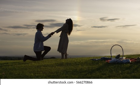 Silhouette man proposes at sunset to his girlfriend