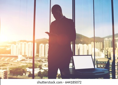 Silhouette of a man proud CEO is searching information in network via cell telephone about the market value of the property. Open laptop computer with empty copy space screen is lying on a table