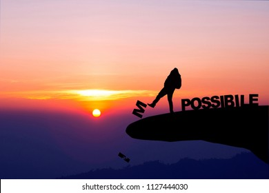 Silhouette man pushing letters I and M from the rock. Word 'possible' standing sound. Sunrise sky at background. Concept of opportunity,copy space.