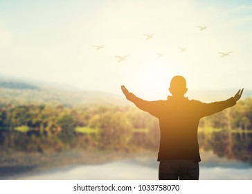 silhouette of a man raise his hand up against sunset sky with flying birds over the lake