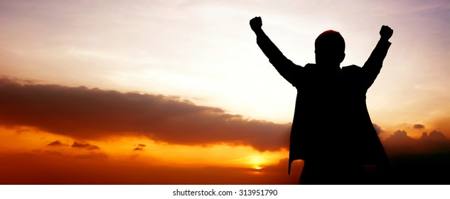 Silhouette of a man raising his arms on twilight sky panoramic (or header) background  - success, winning & accomplished  concepts