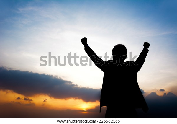 Silhouette of man raising his arms - success, winning & accomplished concept