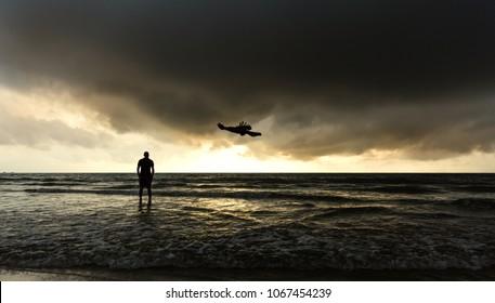 Silhouette of a man and a raven on a beautifully overcast evening. Man enjoying gloomy sunset at Gokarna beach, Karnataka, India. Beach view, Indian ocean, Arabian sea. Coastal place. Cloudy day