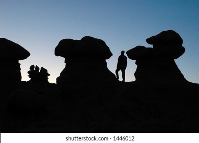 Silhouette of a man in relation to the strange rock formations of Goblin State Park, Utah USA.