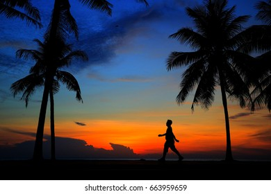 Silhouette man relaxing with sun  effect on sunrise time at beach.