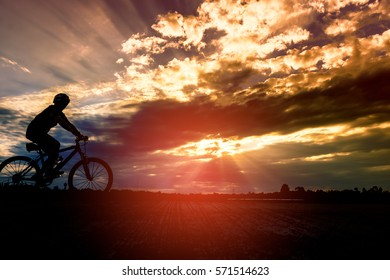 Silhouette a man ride bike at sunset.