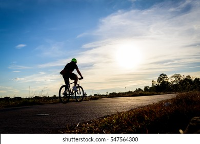 Silhouette  man riding bike at evening.