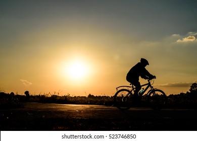 Silhouette a man riding bike at sun set.