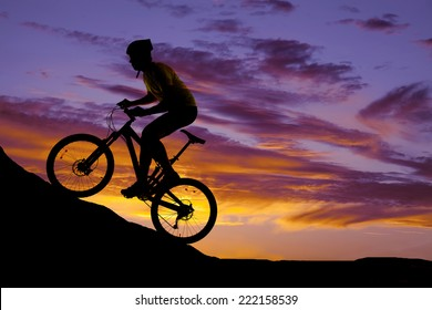 a silhouette of a man riding a mountain bike up a hill.