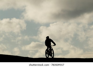 Silhouette of a man riding a mountain bike against a blue cloudy sky on Brean Down, Somerset. Sport concept.