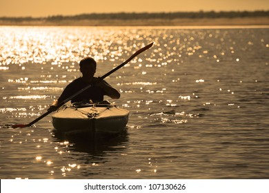 Silhouette of a man rowing in the canoe